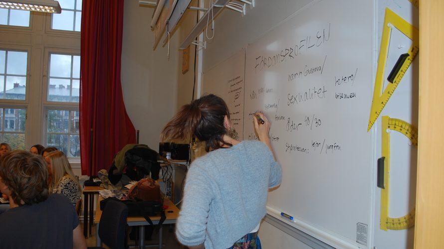 Kvinna skriver på whiteboard.