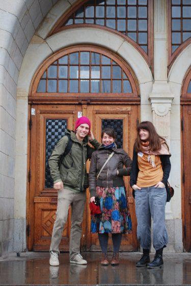 Tre personer framför entrén till S:t Petri skola.
