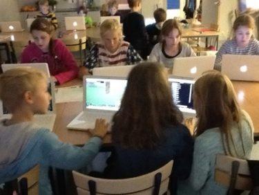 Sju barn sitter runt bord med varsin bärbar dator.