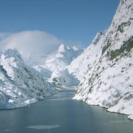 Flod sträcker sig in genom snötäckta berg.