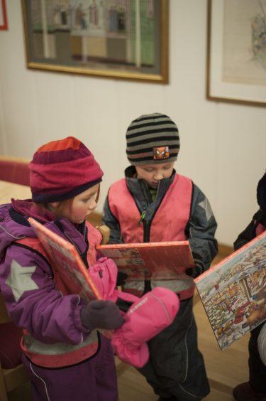 Barn i vinterkläder håller varsin chokladalmanacka i händerna.