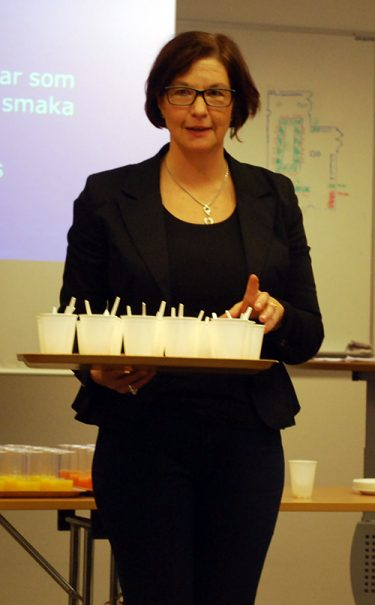 Katarina Stigsdotter håller bricka med vita koppar på.