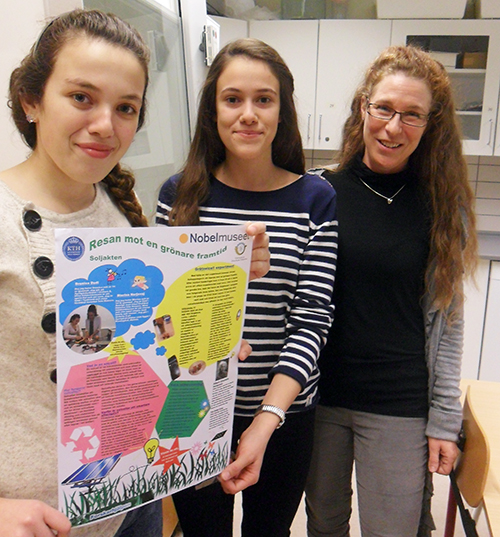 Katarina Fornell och två elever håller upp affisch från nobelmuseet.