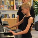 Elev vid dator på biblioteket.