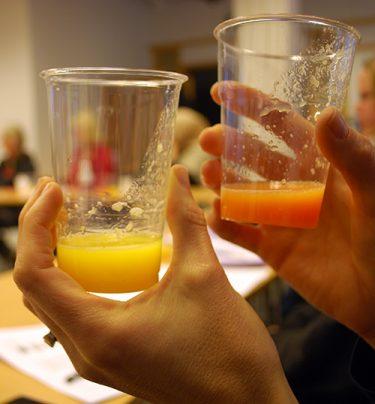 Grön och orange juice i muggar.