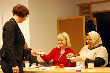 Kvinna bjuder två andra kvinnor på något.