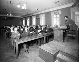Gammal bild där lärare sitter i kateder höjd över eleverna i bänkarna.