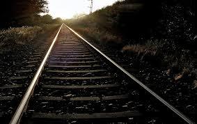 Järnvägsspår leder bort i solnedgång.