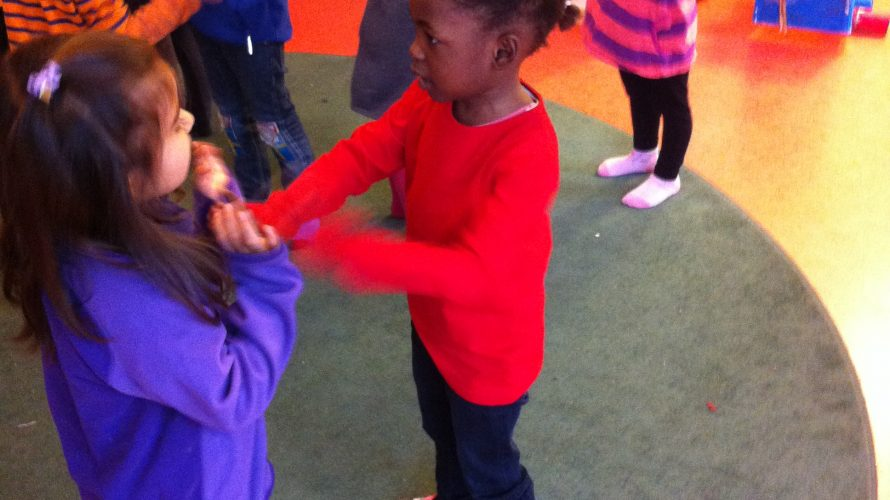 Barn dansar och klappar händer.