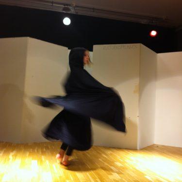 Flicka i svart klänning på scen.