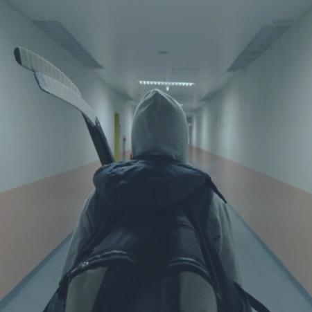 Elev med hockeyklubbor går i korridor.