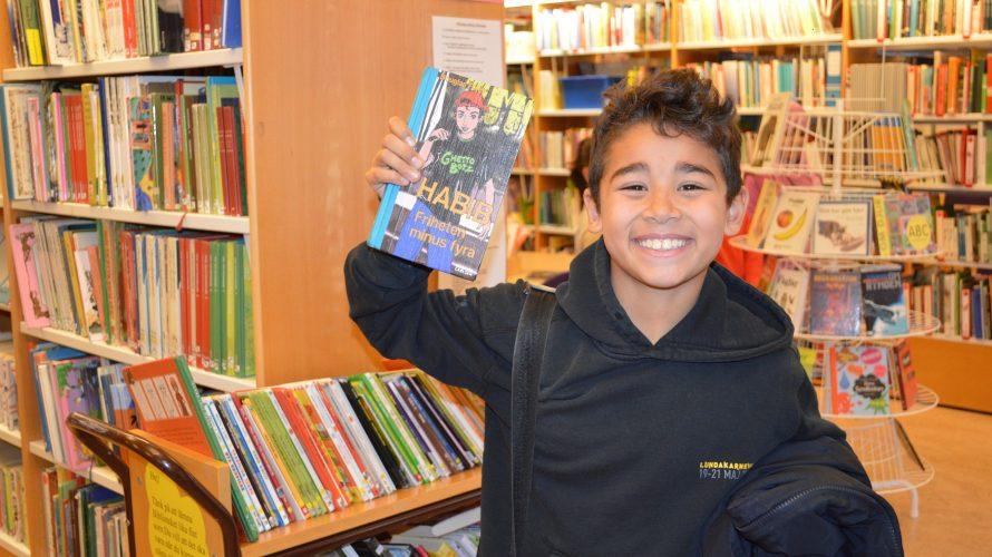 Elev i bibliotek håller glatt upp en bok.