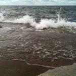 Hav slår in på strand.