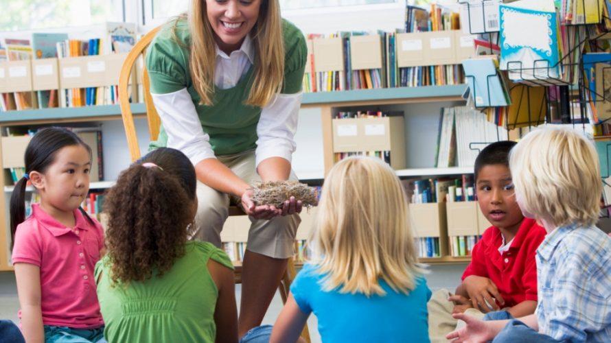 Kvinna visar upp material för barn som sitter på golvet.