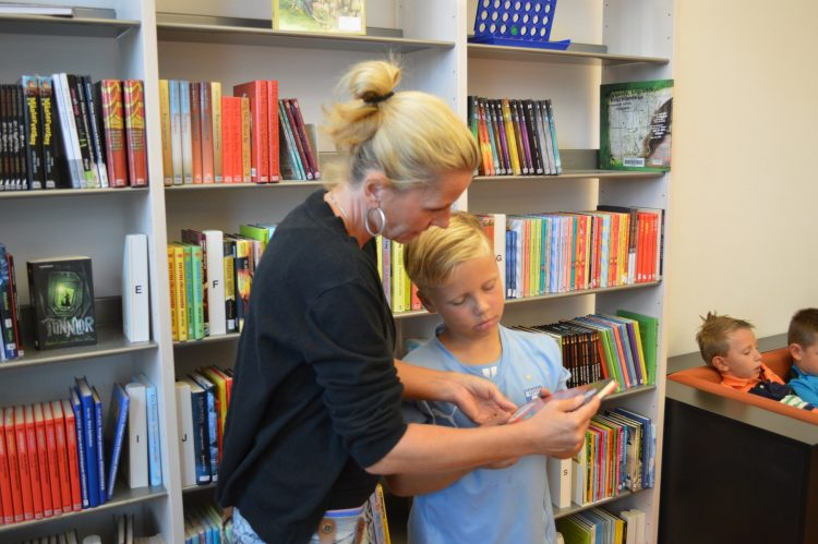 Kvinna visar barn bok.