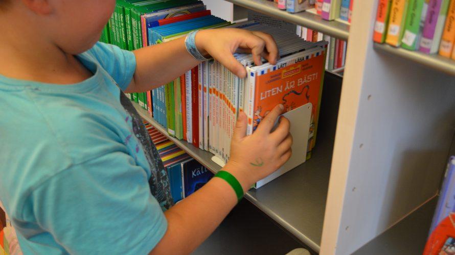 Barn väljer bok i bokhylla.