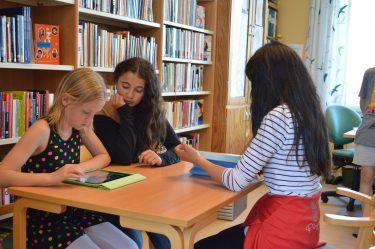 Elever sitter runt bord där en av dem jobbar med ipad.