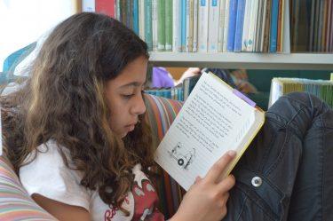 Elev i fåtölj läser.