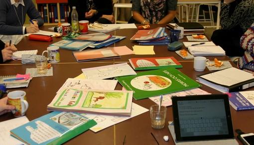Människor sitter runt bord fullt av block och böcker.
