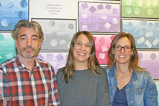 Tre personer framför färgglad vägg.