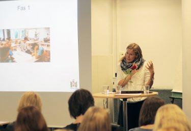 Anna Schylander föreläser framför projicerad presentation.