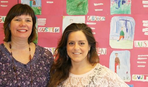 Ann och Bella framför vägg av teckningar.