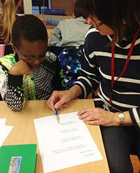 Lärare pekar på papper och visar elev.