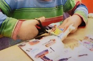 Barn klipper med sax.