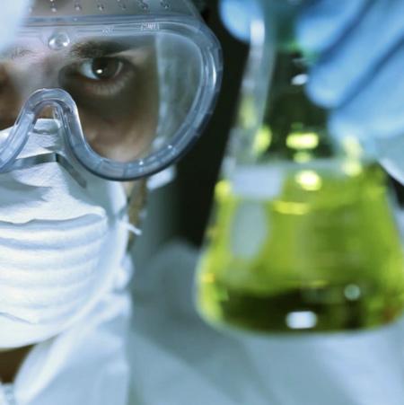 Forskare håller upp provrör med grön vätska.