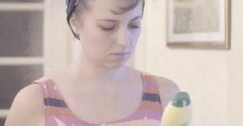 Kvinna tittar på rengöringsmedelsflaska.