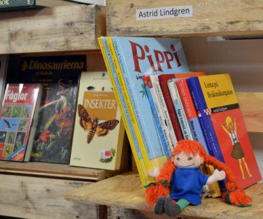 Pippidocka sitter framför böcker.
