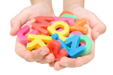 Händer håller fram plastbokstäver.