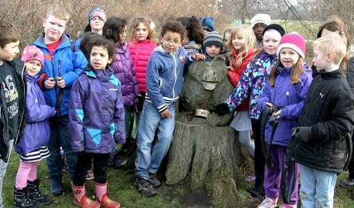 Barn står samlade vid trädstaty.