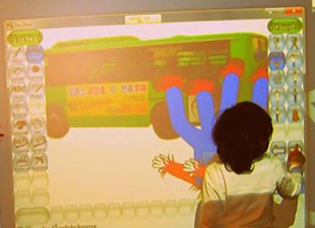 Barn trycker på smartboard.