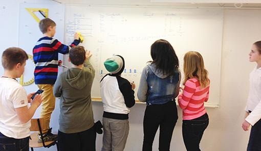 Elever skriver på whiteboard.