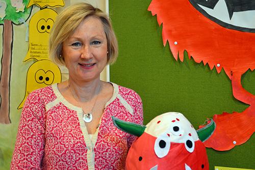 Kvinna håller upp monsterjordgubbe med gröna horn.