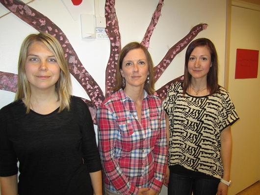 Tre kvinnor framför ett pysslat japanskt träd på väggen.