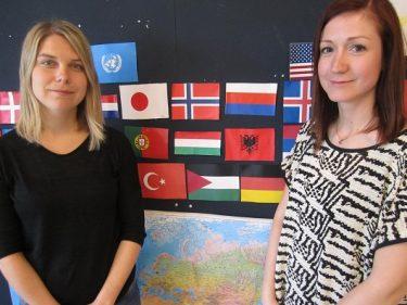 Hanna och Arnella står framför uppsatta flaggor på väggen.