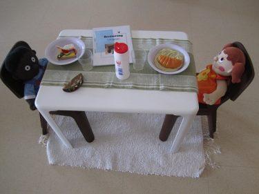 Två små dockor sitter vid bord.