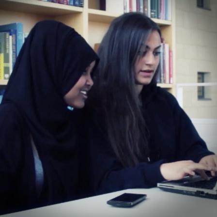 Två elever sitter vid bärbar dator.
