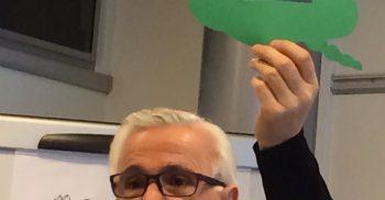 John Polias håller upp grön pratbubbla.