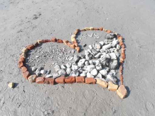 Stenar på strand i form av hjärta.