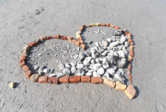 Hjärta format av stenar som ligger på sandstrand.