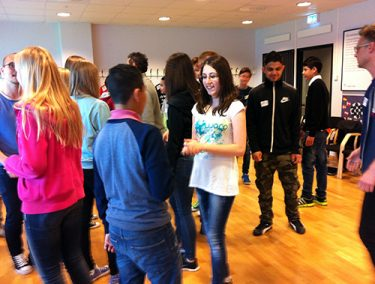 Elever minglar i föreläsningssal.