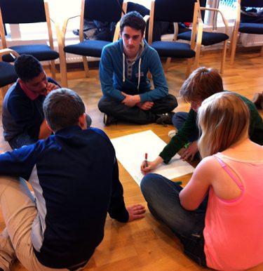Fem elever sitter på golvet och skriver på papper som ligger i mitten.