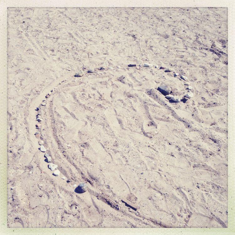 Stenar ligger utlagda i sprial på sandstrand.