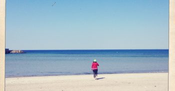 Kvinna springer mot havet på sandstrand.