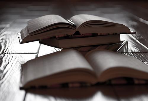 Uppslagna böcker ligger på golv.