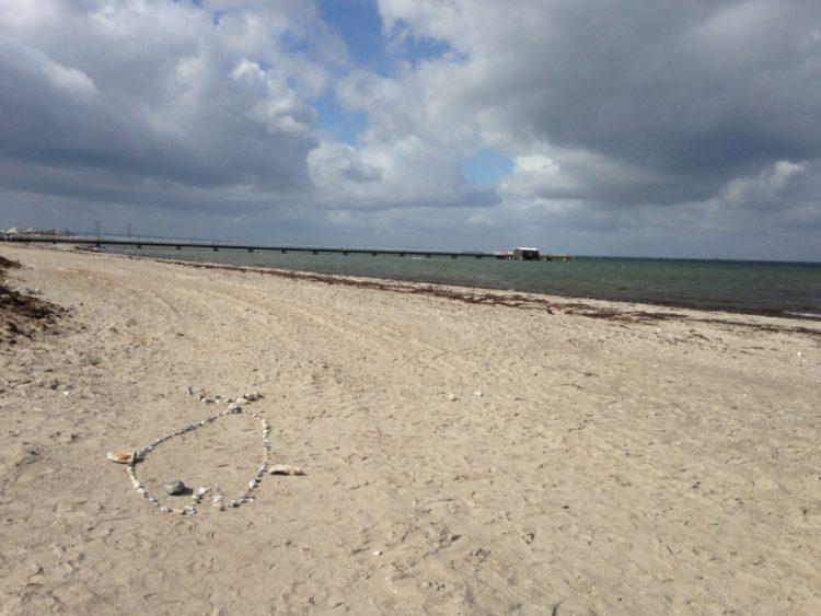 Formen av haj utlagd med sten på sandstranden.