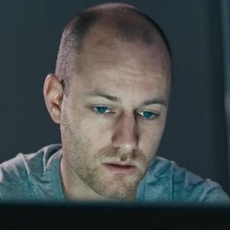 Trött man tittar in i datorskärm.